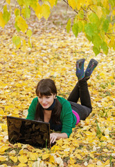young girl with a laptop in a autumn foliage