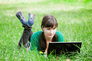girl lying in the grass with laptop