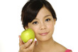 Pretty asian woman with green apple isolated