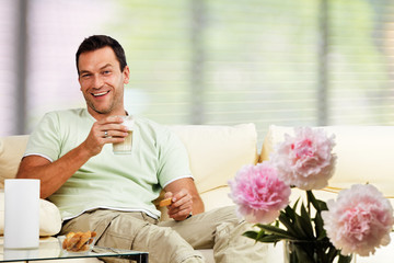 man relaxing in the living room, with latte macchiato