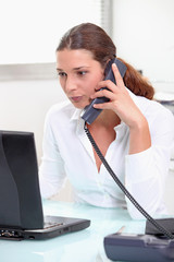 Serious brunette using an office phone