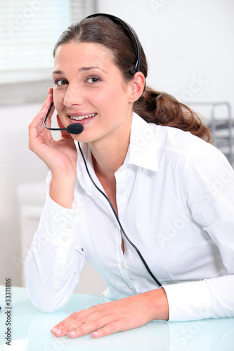 Smiling young woman using a headset
