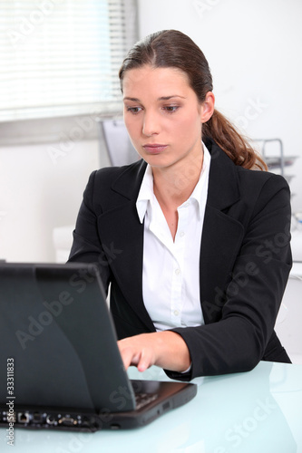 Serious young businesswoman using a laptop