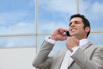 Business man stood outdoors using mobile telephone