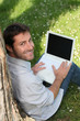 Smiling man in a park, using a laptop