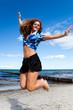 junge Frau springt ausgelassen am Strand