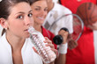 Sporty young girl drinking bottled water
