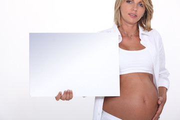 Pregnant blond model holding message board