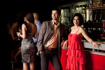 man and woman posing beside bar