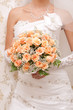 Bride holding orange bouquet detail