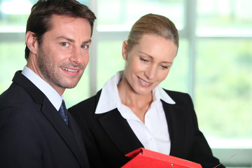Businessman and woman looking at folder
