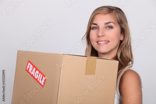 Young woman with a cardboard box marked FRAGILE
