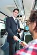 Leinwandbild Motiv Smiling conductor checking tickets on a tram