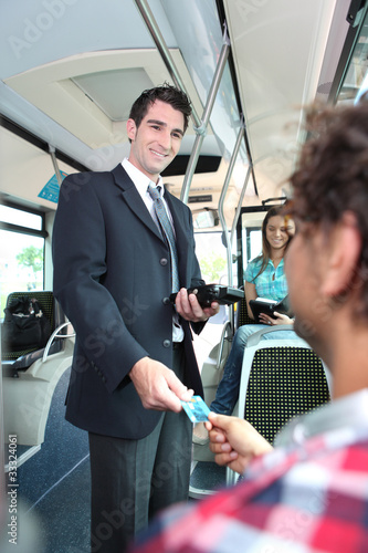 Smiling conductor checking tickets on a tram