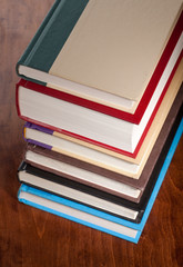 Six books stacked neatly on a table