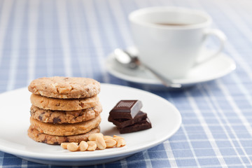 Peanut cookies with chocolate and cup of coffee or tea.