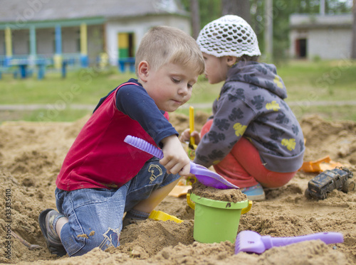 Boy and girl play in the sandpit in the playground