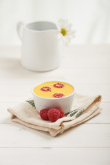 raspberry custard on a napkin, in background white flower