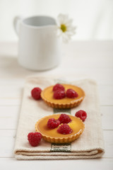 raspberry tart on a napkin, in background white flower