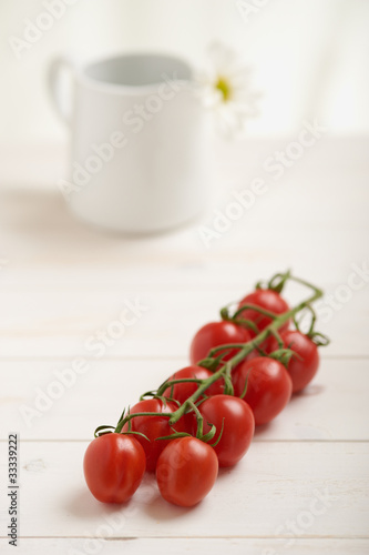 Cherry tomatoes on a white table, white flower in background