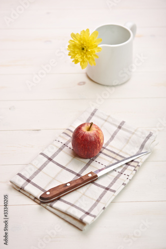 red apple on a white table, in backgroiund a flower