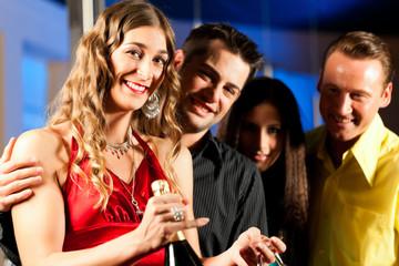 Leute mit Drinks in Bar oder Club