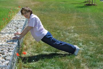 Seniorin im Freien macht Körperübungen