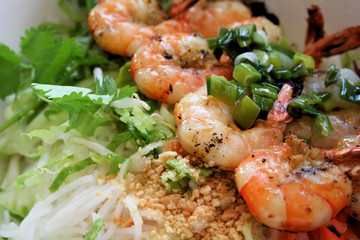 Grilled shrimp on bed of rice noodles and greens.