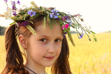 girl with flowers diadem on her head posing at the field.