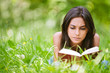 Woman lies on grass and reads book