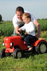 Vater und Sohn mit rotem Traktor
