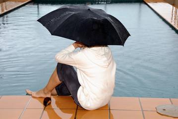 Frau sitzt am Schwimmbad im Regen