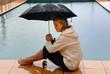 Frau sitzt am Pool im Regen