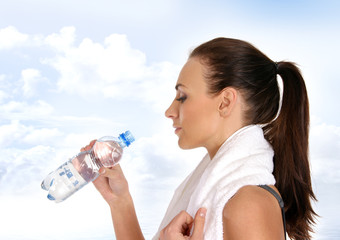 A young and fit brunette woman drinking fresh water