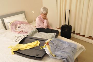 Ältere Frau packt Reisekoffer