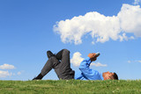 businessman with digital tablet laying down at the park