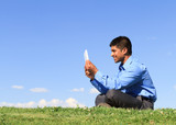 businessman with digital tablet sitting down at the park