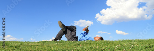 businessman with tablet on grass, panorama