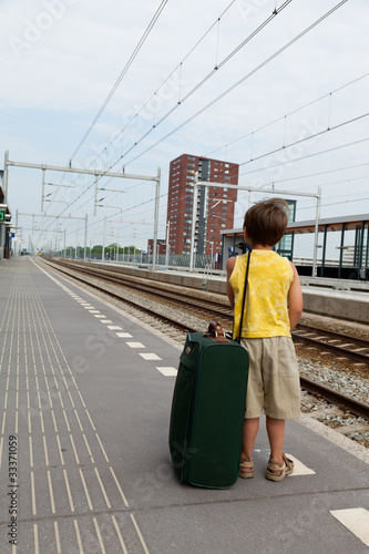 Young boy with luggage waiting for train