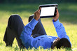 businessman with digital tablet laying down on grass