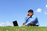 businessman with cell phone and laptop at the park