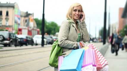 woman with shopping bags in the city talking on the phone