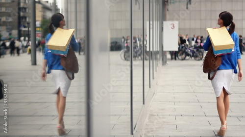 Attractive woman with shopping bags looking at shop window © Radoslaw Frankowski