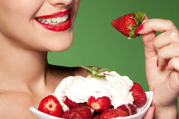 Female going to eat strawberry, on green background