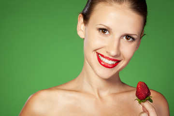Close-up portrait of young female going to eat strawberry