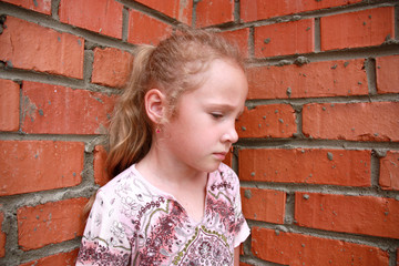 sad child in front of a brick wall
