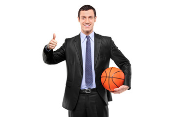 Happy businessman holding a basketball and giving thumb up