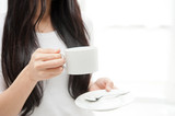beautiful asian woman taking a cup of coffee