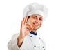 Smiling chef isolated on white showing ok hand sign