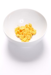 Bowl with a little of cornflakes over white background